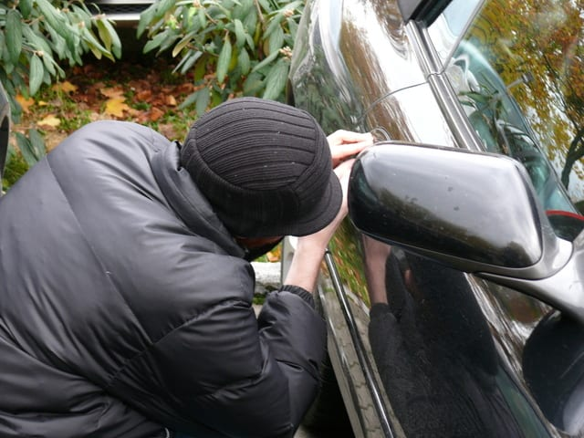 Robber trying to open a car